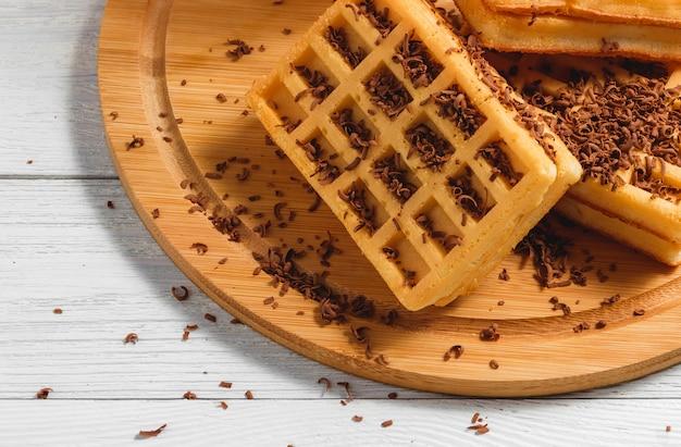Gaufres faites maison avec confiture et chocolat sur une vieille table en bois.