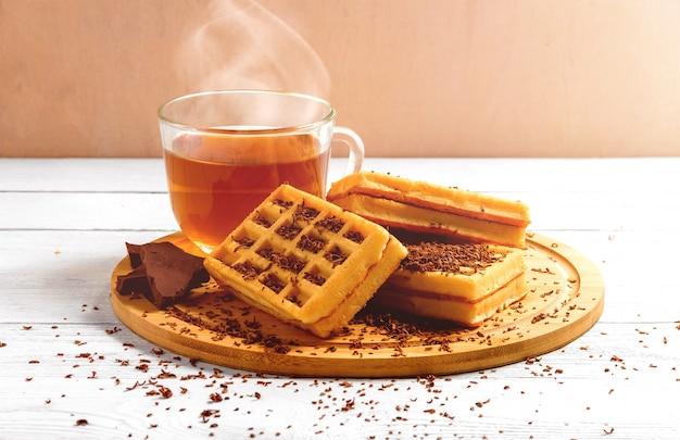 Gaufres faites maison avec de la confiture sur une vieille table en bois. gaufrettes avec tasse de thé, théière, chocolat.