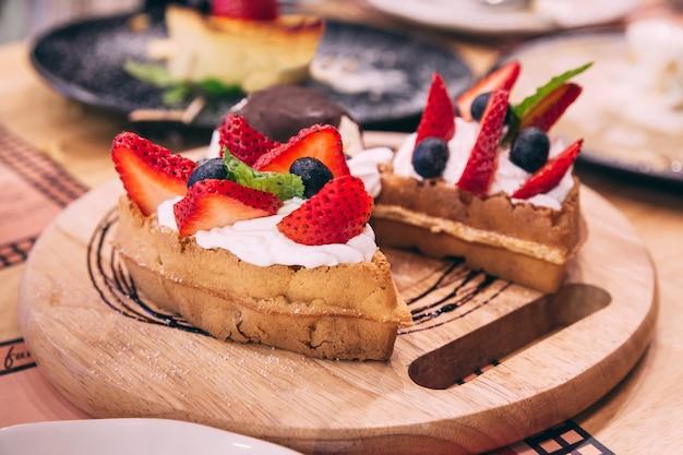 Gaufres garnies de tranches de fraise et de mûre servies avec une boule de glace
