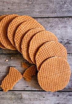 Gaufres hollandaises traditionnelles au caramel sur le fond en bois, vue de dessus.