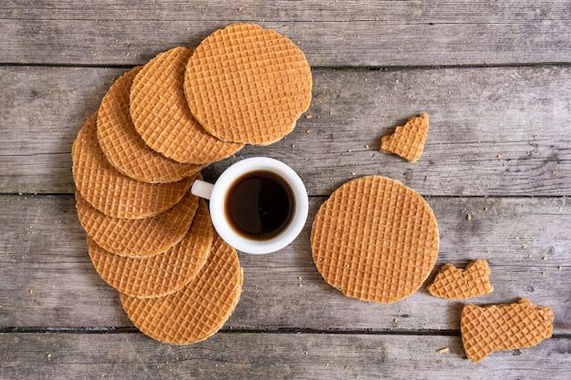 Gaufres hollandaises traditionnelles au caramel et tasse de café sur le fond en bois, vue de dessus.