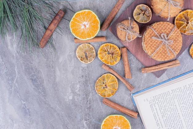 Gaufres de hollande avec des biscuits sur une planche de bois avec des tranches d'orange sèches et de cannelle autour