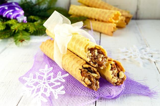 Gaufres maison au miel sous forme de tubes fourrés au caramel et aux noix sur fond clair. fermer