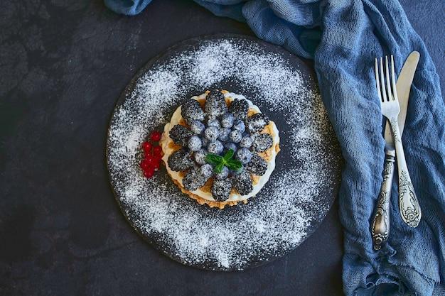 Gaufres maison aux myrtilles et mûres, sucre en poudre sur une assiette en pierre avec des fruits. faible profondeur de champ.
