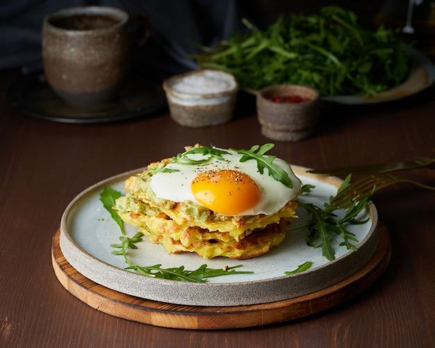 Gaufres de pommes de terre avec œuf au plat, roquette et sauce à l'avocat. petit déjeuner copieux et gras. table marron foncé.