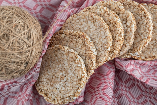 Gaufres de riz avec une pelote de laine sur une nappe.