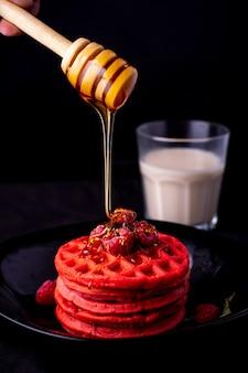 Gaufres rouges saines avec fruits et miel sur plaque noire et fond noir sous différents angles