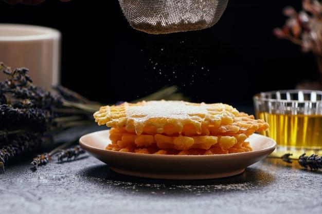 Gaufres saupoudrées de sucre glace sur fond sombre, gros plan