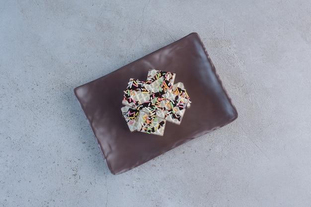 Gaufres à la vanille croustillantes décorées de pépites sur plaque sombre.