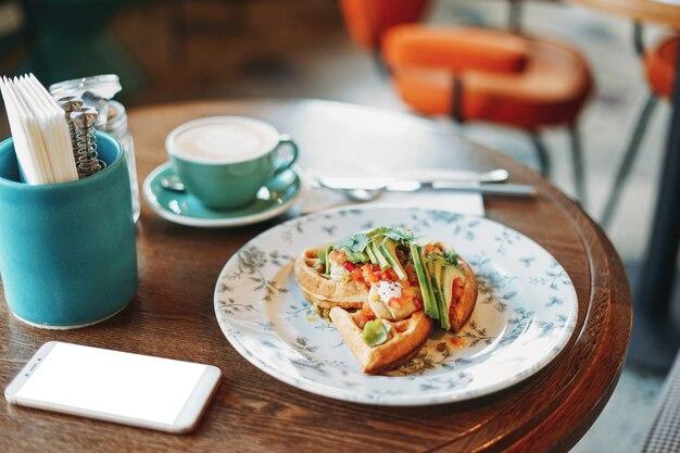 Gaufres végétariennes légumes frais et déjeuner d'affaires avocat avec café téléphone mobile écran blanc à table au café