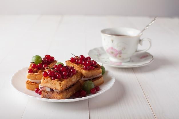 Gaufres viennoises avec baies et une tasse de thé debout sur la table