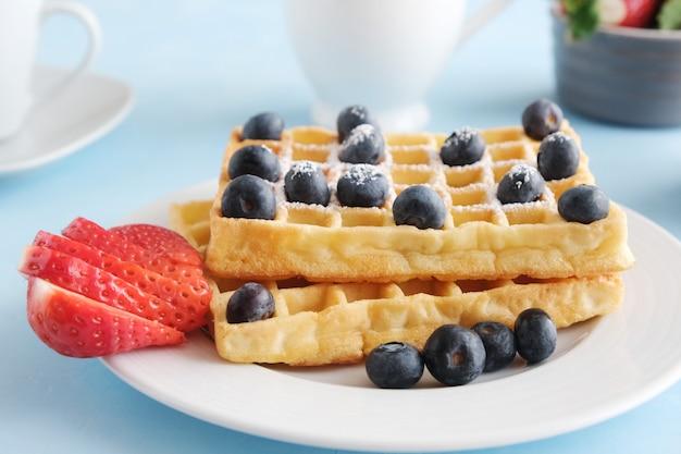 Gaufres viennoises ou belges fraîchement chantées avec des fraises et des bleuets frais
