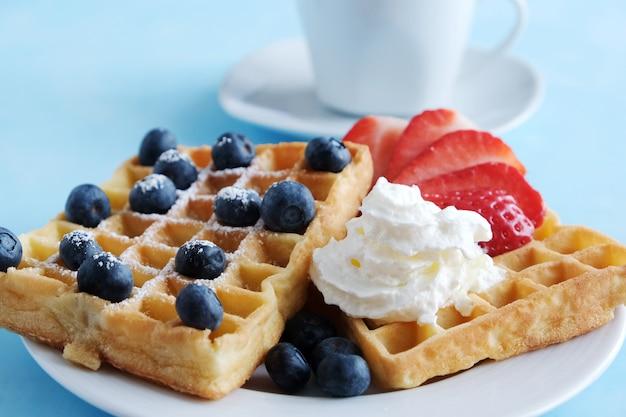 Gaufres viennoises sur une plaque blanche avec des fraises et des bleuets biologiques frais