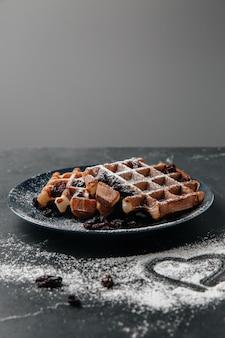 Gaufres viennoises, saupoudrées de sucre en poudre, sur une table texturée foncée