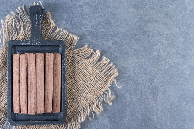 La gaufrette au chocolat roule dans une planche sur une texture sur la surface en marbre