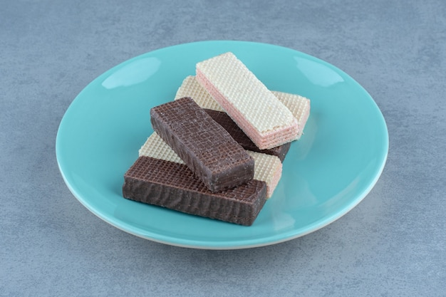 Gaufrettes au chocolat et au caramel sur plaque verte sur gris.