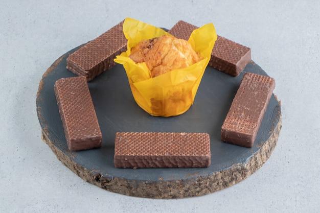 Gaufrettes au chocolat autour d'un petit gâteau sur une planche sur fond de marbre.