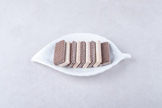 Gaufrettes aux fraises et au chocolat sur une assiette sur une table en marbre.