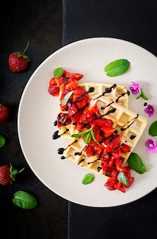 Gaufrettes de belgique avec des fraises, du chocolat et du sirop sur une plaque. mise à plat. vue de dessus.