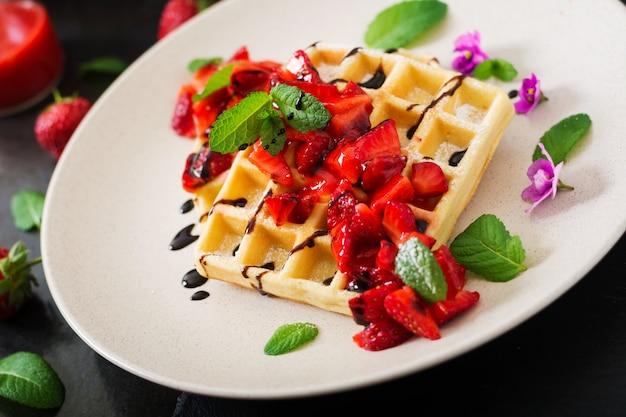 Gaufrettes de belgique avec des fraises, du chocolat et du sirop sur une plaque.