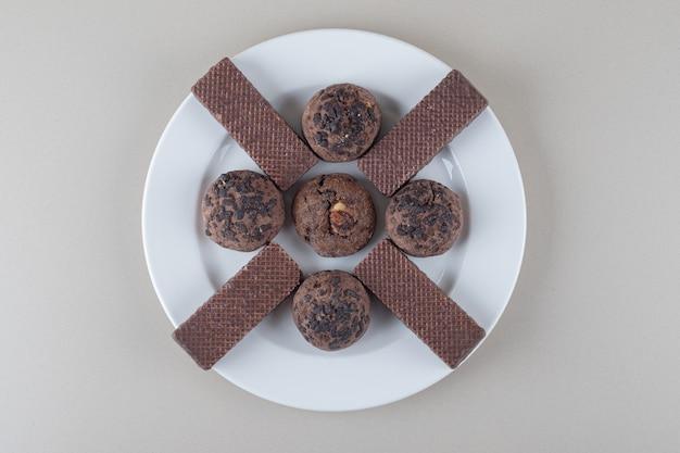 Gaufrettes enrobées de chocolat et biscuits aux pépites de chocolat sur un plateau sur fond de marbre.