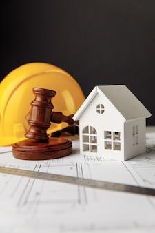 Gavel et plans de construction avec casque jaune et image verticale de la maison