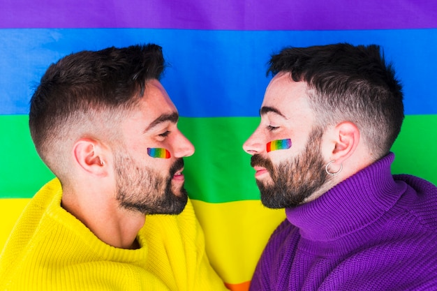 Gays avec emblèmes arc-en-ciel se regardant