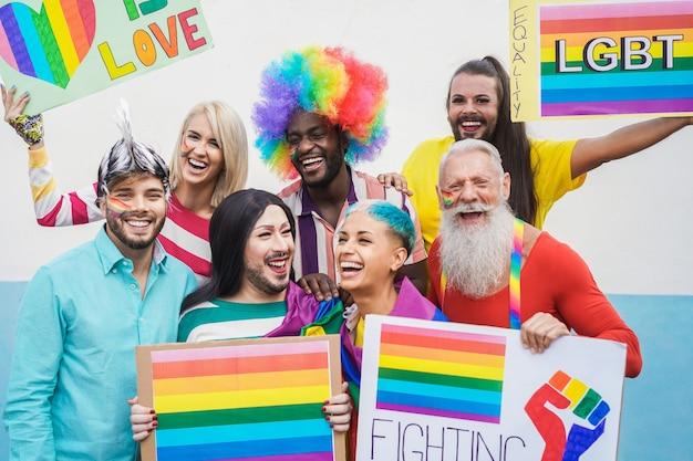 Les gays s'amusant à la parade de la fierté avec des drapeaux lgbt à l'extérieur