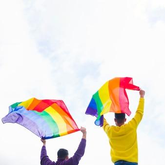 Gays tenant des drapeaux arc-en-ciel en hauteur