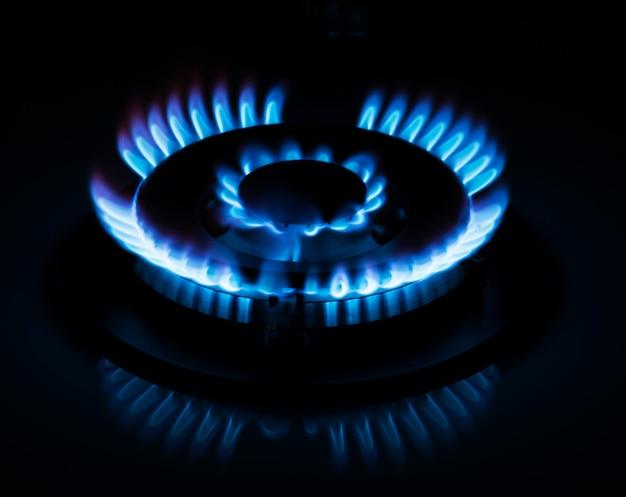 Le gaz naturel brûle sur une cuisinière à gaz de cuisine dans l'obscurité
