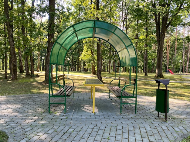 Gazebo avec bancs et table en forêt pour se détendre