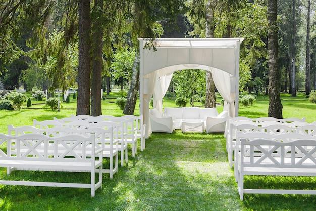 Gazebo blanc et rangées de bancs sur la pelouse du parc