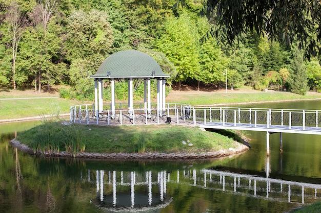 Gazebo avec pont forgé, étang et fond de paysage d'été.