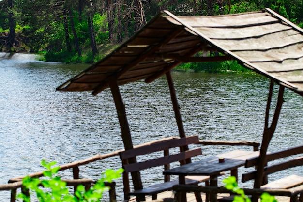 Gazebo relaxant construit sur la rivière contre la forêt.