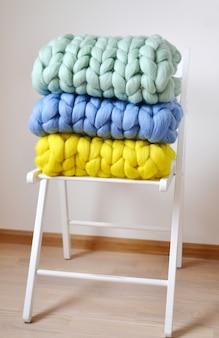 Géant rose menthe jaune bleu couverture plaid laine mérinos tricoté sur blanc tabouret en bois chaise intérieur de la maison