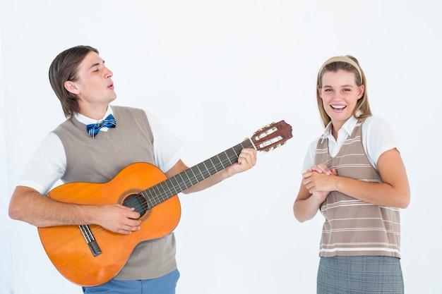 Geek hipster sérénade sa copine avec guitare