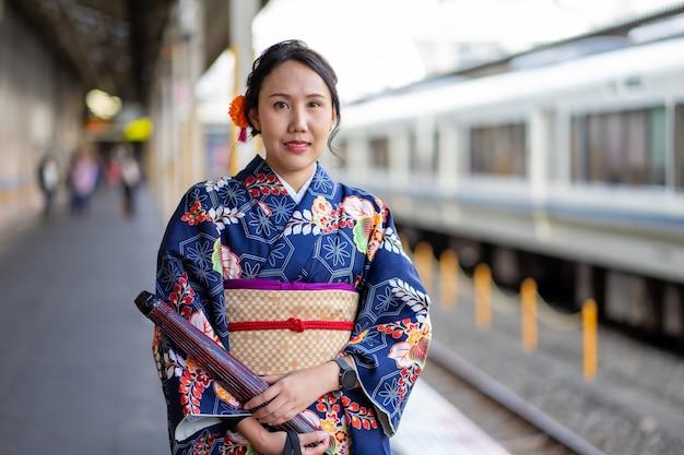 Geisha portant un kimono japonais dans la gare de kyoto
