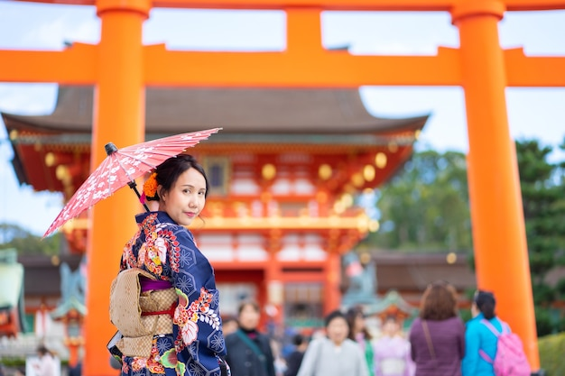 Geishas girl wearing kimono japonais parmi tori gate en bois rouge au sanctuaire fushimi inari