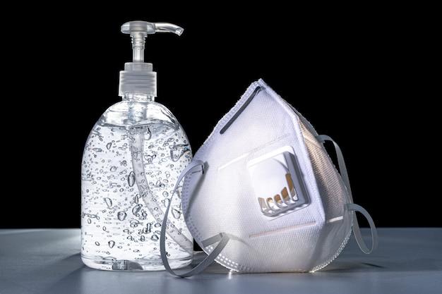 Gel anti-septique pour les mains et masque facial n95 sur tableau blanc avec rétro-éclairage et fond noir