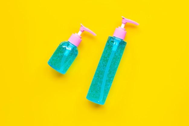 Gel désinfectant pour les mains à l'alcool dans des bouteilles de pompe sur fond jaune.