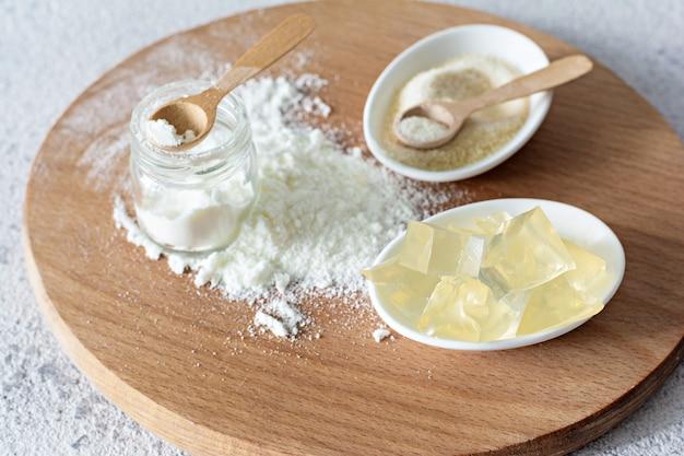 Gélatine, agar-agar, masse gélatineuse (cubes sous forme de cristaux) sur fond gris. agent gélifiant (collagène) pour les produits culinaires et de confiserie.