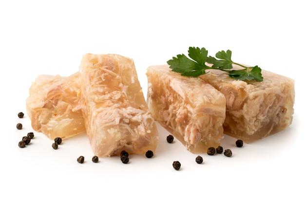 Gelée de viande coupée en tranches avec les feuilles de persil et de poivre noir sur blanc, gros plan.