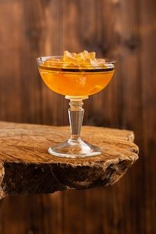 Gelées d'orange à l'intérieur du verre sur bois brun