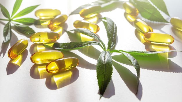 Gels souples de gélatine d'huile de lin et de lin avec des feuilles vertes.
