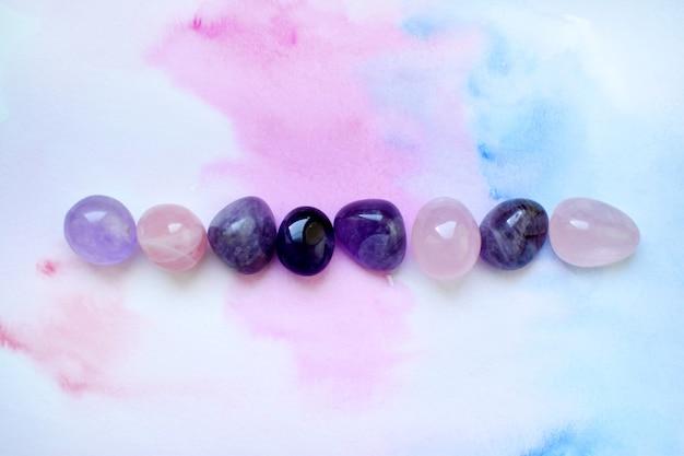 Gemmes de différentes couleurs. améthyste et quartz rose sur fond bleu-rose.