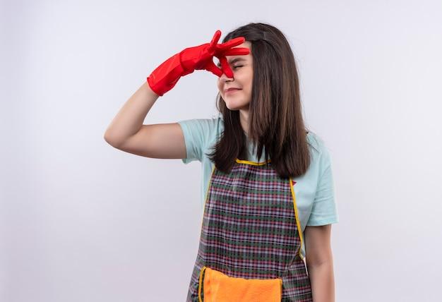 Gêné jeune belle fille portant un tablier et des gants en caoutchouc fermant le nez entre les yeux fermés