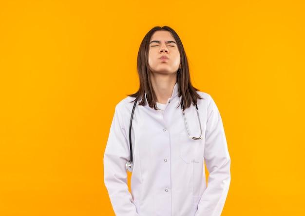 Gêné jeune femme médecin en blouse blanche avec stéthoscope autour de son cou soufflant les joues avec les yeux fermés debout sur le mur orange