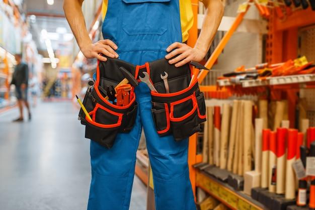 Générateur de sexe masculin essayant sur la ceinture à outils à l'étagère en quincaillerie. constructeur en uniforme regarde les marchandises dans la boutique de bricolage
