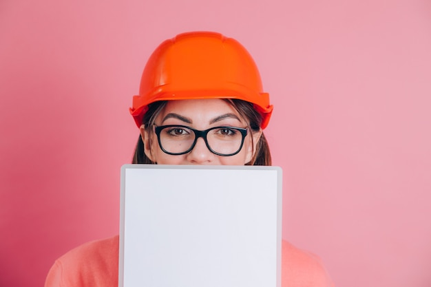 Générateur de travailleur femme souriante tenir panneau blanc vide sur fond rose. casque de construction.