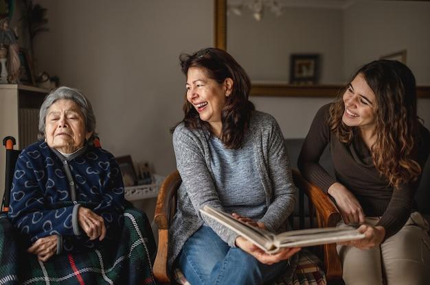 Génération de femmes avec vieille grand-mère malade assise en fauteuil roulant et fille souriante et petite-fille à la recherche d'un album photo.